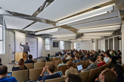 A photo of a large lecture hall in the Simons Institute. There is a person at the front of the hall talking and many people sitting in seats.