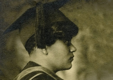 Side profile of Annie Coker wearing a graduation cap and gown