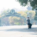 A student in a mask wheels his belongings onto campus near Sather Gate, with smoke from the Northern California wildfires visible in the air.