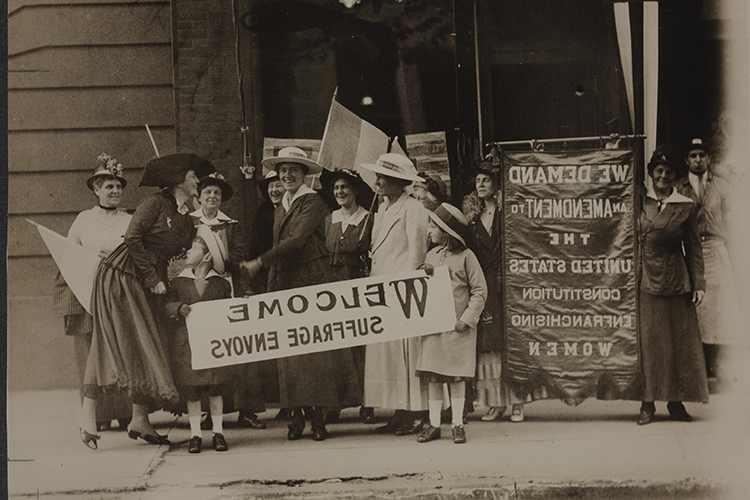 Archival photo of women holding women's suffrage signs
