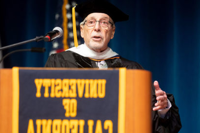 "A photo of Geoffrey Nunberg at the 2019 I School Commencement. He is wearing academic regalia and standing behind a podium that says ""University of California"""