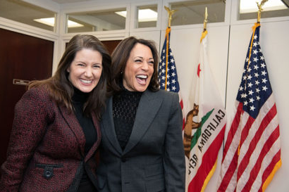 Kamala Harris and Libby Schaaf smile in front of a California flag